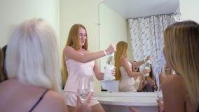 Feiern Sie Partei, bezaubernde nette Mädchen mit dem langen Haar im offenen Champagner der Pyjamas im Raum mit Spiegel auf Sommer stock video