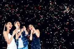 Feierparteigruppe asiatische junge Leute, die Konfettis h halten Stockfoto