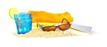 Feiertag auf dem Strand mit Tüchern, Sonnenbrille, einem Buch und einem Getränk Lizenzfreies Stockfoto