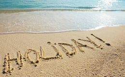 Feiertag - es wird auf Sand vor einer Welle geschrieben Stockfoto