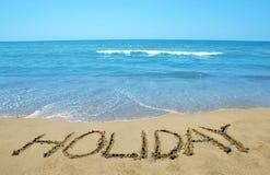 Feiertag geschrieben auf sandigen Strand Lizenzfreie Stockbilder