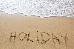 Feiertag geschrieben in Sand Lizenzfreie Stockfotos
