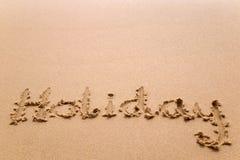 Feiertag geschrieben in Sand Stockbild