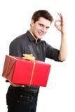 feiertag Mann, der die rote Geschenkbox sich zeigt Daumen gibt Lizenzfreie Stockfotos