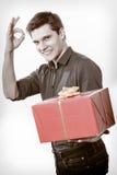 feiertag Mann, der die rote Geschenkbox sich zeigt Daumen gibt Stockfotografie