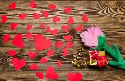 Feiertag/romantischer/Hochzeits-/Valentinstaghintergrund mit Plüsch stiegen, Geschenkbox, kleine Herzen und Goldband auf Holztisc Stockfotos