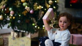 Feiertag, Weihnachten Kleines Mädchen rüttelt das Geschenk vor, es zu öffnen stock video