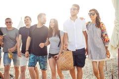 Feiertage, Ferien Gruppe Freunde, die Spaß auf Strand, dem Gehen, Getränkbier, dem Lächeln und dem Umarmen haben lizenzfreie stockfotos