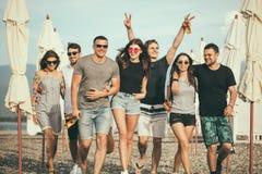 Feiertage, Ferien Gruppe Freunde, die Spaß auf Strand, dem Gehen, Getränkbier, dem Lächeln und dem Umarmen haben stockfoto