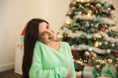 Feiertags-, Feier- und Leutekonzept - junge Frau über Weihnachtsinnenraumhintergrund stockfotografie