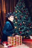 Feiertags-, Feier- und Leutekonzept - lächelnde Frau im Kleid, das rote Geschenkbox über Weihnachtsbaum hält, beleuchtet Stockbilder