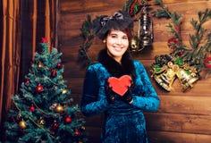 Feiertags-, Feier- und Leutekonzept - lächelnde Frau im Kleid, das rote Geschenkbox über Weihnachtsbaum hält, beleuchtet Lizenzfreie Stockbilder