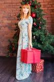 Feiertags-, Feier- und Leutekonzept - lächelnde Frau im Kleid, das rote Geschenkbox über Weihnachtsbaumhintergrund hält Lizenzfreie Stockfotos