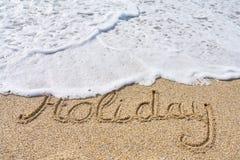 Feiertagsaufschrift auf einem tropischen sandigen Strand mit Wellen auf einem Hintergrund lizenzfreies stockfoto