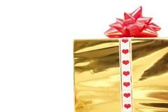 Feiertagsgeschenk im Kasten mit Goldfolie und rotem Bogen Stockbilder