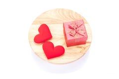 Feiertagsgeschenk und rote Herzen auf hölzernem Hintergrund lizenzfreies stockbild