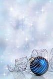 Feiertagshintergrund mit einer blauen Weihnachtsverzierung und -band lizenzfreies stockbild
