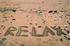 Feiertagshintergrund mit ENTSPANNEN sich das Wort, das auf sandigen Strand geschrieben wird Dieses ist Datei des Formats EPS10 So Lizenzfreies Stockfoto