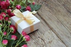 Feiertagshintergrund mit rosa Rosen und Geschenkbox über hölzernem tabl Stockbild