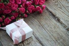 Feiertagshintergrund mit rosa Rosen und Geschenkbox über hölzernem tabl Lizenzfreie Stockfotos