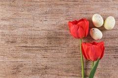 Feiertagshintergrund mit roten Tulpen und Ostereier auf hellbraunem Hintergrund Text sperren Draufsicht Stockbilder