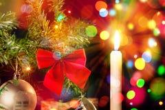 Feiertagskarte mit Kerze und Verzierungen auf Weihnachtsbaum Stockfoto