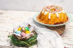 Feiertagskleiner kuchen, farbige Eier in einem Nest, christlicher traditioneller Feiertag Ostern lizenzfreie stockfotos