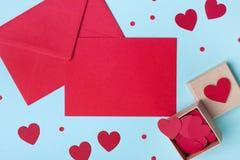 Feiertagsmodell für Valentinsgrußtag Boxen Sie voll von den roten Herzen und von der Papierkarte mit Umschlag auf blauer Tischpla stockfotos