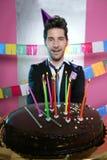 Feiertagsparty-Schokoladenkuchen in den Händen des jungen Mannes Stockfotos