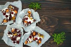 Feiertagsschokoladenbarke mit Trockenfrüchten und Nüssen auf einem dunklen hölzernen Hintergrund Beschneidungspfad eingeschlossen Lizenzfreie Stockfotografie