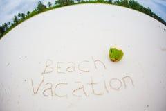 Feiertagssommerkonzept Die Wortstrandferien geschrieben auf den Sand Stockfoto