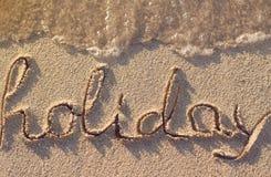Feiertagswort auf Strand Stockfotos