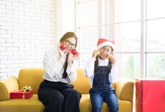 Feierweihnachtsfeiertag, asiatische Schwester, die zu Hause Ball mit jüngerer Schwester spielen, glücklich und dem Lächeln lizenzfreie stockfotos