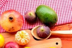 Feige, Granatapfel, Apfel und Mandarinen (Tangerinen) auf rauem Hintergrund Lizenzfreie Stockfotos