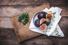 Feigen im flachen Teller auf choppingboard und Serviette in der rustikalen Art Stockbild