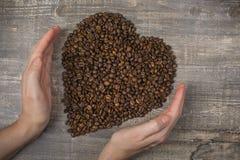 Feijão de café à disposição e coração uma tabela de madeira Fundo bonito Fotografia de Stock Royalty Free