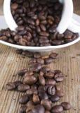 Feijão de café derramado na prancha velha Imagens de Stock