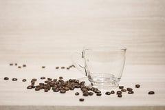 Feijão de café e copo de café vazio na terra traseira de madeira Imagem de Stock
