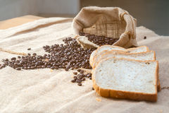 Feijão de café no saco e no pão cortado Fotografia de Stock