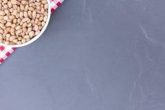 Feijão do amendoim na bacia isolada No fundo preto, vista superior Fotos de Stock Royalty Free