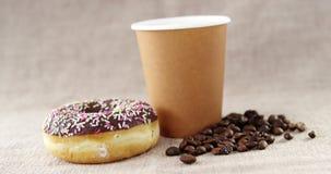 Feijão o copo de café e da filhós e de café descartáveis do chocolate com polvilham filme