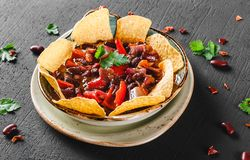 Feijão vermelho com nachos ou microplaquetas do pão árabe, pimenta e verdes na placa sobre o fundo escuro Petisco mexicano, alime imagem de stock