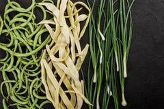 Feijões crus saudáveis dos vegetais do vegetariano do verão, os verdes e os amarelos, cebolas no fundo de pedra escuro imagens de stock