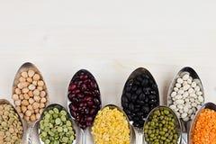 Feijões da leguminosa da variedade nas colheres com espaço da cópia no fundo de madeira branco Imagem de Stock Royalty Free