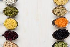 Feijões da leguminosa da variedade nas colheres com espaço da cópia no fundo de madeira branco Foto de Stock Royalty Free