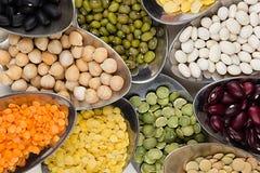 Feijões da leguminosa da variedade nas colheres macro no fundo de madeira branco Imagens de Stock Royalty Free