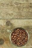 Feijões da xícara de café na tabela de madeira velha Vendas do café Decorações para o menu Copos de café e feijões de café fresco Imagens de Stock Royalty Free