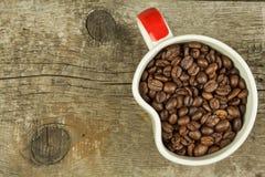 Feijões da xícara de café na tabela de madeira velha Vendas do café Decorações para o menu Copos de café e feijões de café fresco Fotos de Stock Royalty Free
