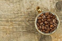 Feijões da xícara de café na tabela de madeira velha Vendas do café Decorações para o menu Copos de café e feijões de café fresco Foto de Stock Royalty Free