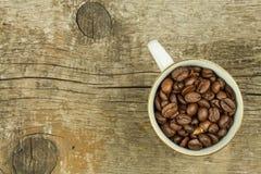 Feijões da xícara de café na tabela de madeira velha Vendas do café Decorações para o menu Copos de café e feijões de café fresco Foto de Stock